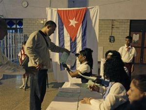 An election official gives a man ballot papers at a special polling station set up in Havana's main train station February 3, 2013. Cubans go to polls to elect National Assembly representatives.